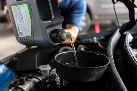 Automonteur of monteur vult een nieuwe motorolie smeermiddel bij de garage voor reparatie of onderhoud van een auto