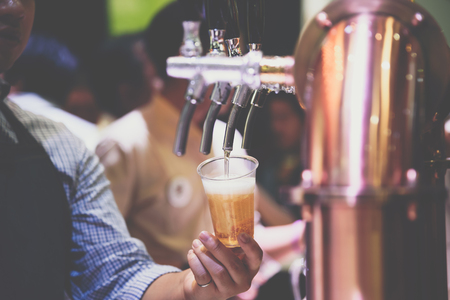 Barman or bartender pouring a draught lager beer from beer tap on counter for serving in a restaurant or pub. Stock Photo