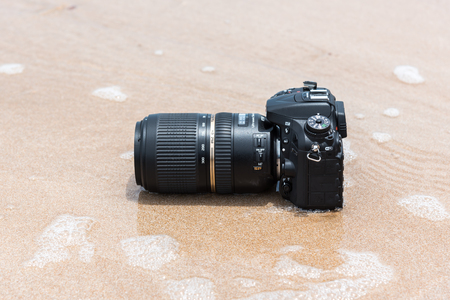 Rayong, Thailand - May 27, 2017 : Unidentified photographer demo waterproof DSLR camera with telephoto lens on beach it wet from water sea wave when travel and test using in the extreme environment Editorial