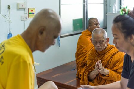 Chanthaburi, Thailand - October 14, 2018 : Luang Pu Ong Thawaro, famous monk of Tham Khao Maze Monastery come to visit elderly man 70s cancer patient chemotherapy to treat cancer at hospital