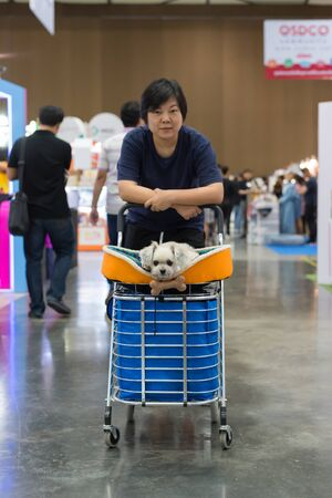 Bangkok, Thailand - July 1, 2017 : Unidentified asian woman feeling happy when her and her pet (The dog) on shopping cart allowed to entrance for exhibit hall or expo