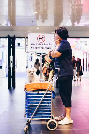 Bangkok, Thailand - July 1, 2017 : Unidentified asian woman feeling shocked when her and her pet (The dog) on shopping cart found warning sign No Pets Allowed at entrance door for exhibit hall or expo