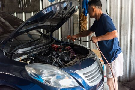 Bangkok, Thailand - October 10, 2018 : Unidentified car mechanic or serviceman cleaning the car engine after checking a car engine for fix and repair problem at car garage or repair shop