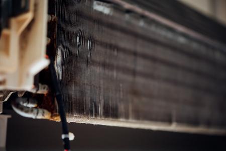Arbeiter zum Reinigen des Spulenkühlers der Klimaanlage mit Wasser zum Reinigen eines Staubs an der Wand im Haus des Kunden beim Wartungsservice maintenance