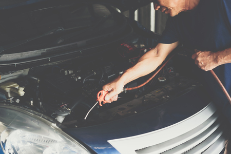 Car mechanic or serviceman cleaning the car engine after checking a car engine for fix and repair problem at car garage or repair shop Banco de Imagens - 124967440
