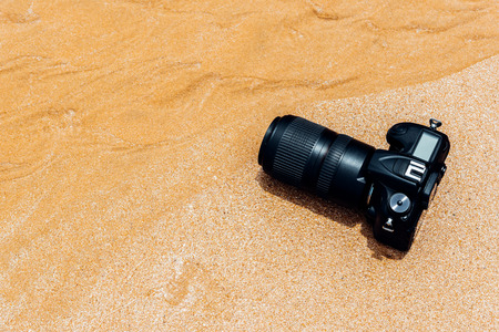 DSLR camera with telephoto lens on a beach it wet from water sea wave when travel and test using in the extreme environment demo waterproof by photographer