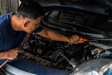 Car mechanic or serviceman cleaning the car engine after checking a car engine for fix and repair problem at car garage or repair shop Banco de Imagens