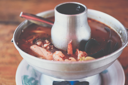 Prawn seafood spicy soup (Tom Yum Goong) is a famous Thai food have a spicy in Thai street food market at Bangkok Thailand