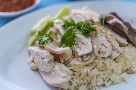 Rice steamed with chicken soup (hainanese chicken rice) with cucumber, liver and sauce for sale at Thai street food market or restaurant in Bangkok Thailand
