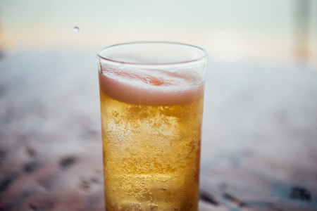 Fresh cold beer water in to beer glass with ice and froth in brewery pub or restaurant on a wood table