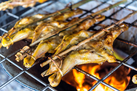 Grilled chicken sauce is a Thai barbeque food by chicken and sauce cooking on charcoal with flames at Thai street food market Stock Photo