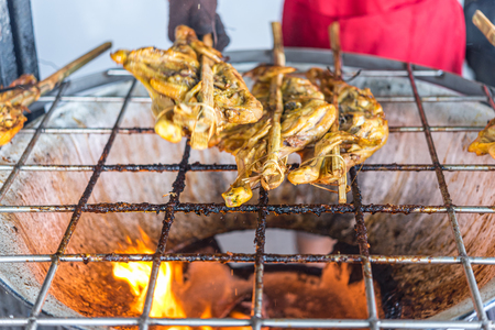 Grilled chicken sauce is a Thai barbeque food by chicken and sauce cooking on charcoal with flames at Thai street food market Reklamní fotografie