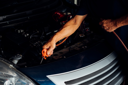 Car mechanic or serviceman cleaning the car engine after checking a car engine for fix and repair problem at car garage or repair shop Imagens