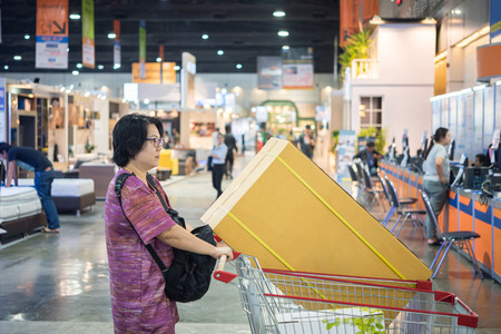 Asian woman feeling happy when her purchase a big product with cartons in shopping cart in department store or exhibit hall expo