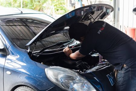 Bangkok, Thailand - October 7, 2018 : Unidentified car mechanic or serviceman checking a car engine for fix and repair problem at car garage or repair shop Editöryel