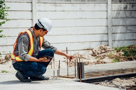 Asian man civil construction engineer worker or architect with helmet and safety vest working and holding a tablet computer