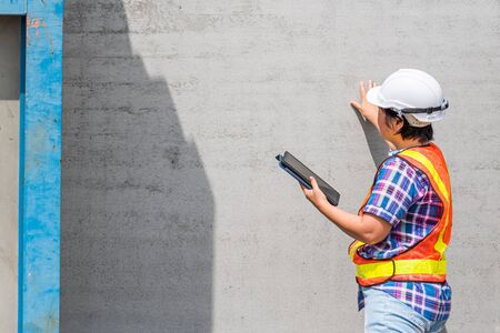 Asian woman civil construction engineer worker or architect with helmet and safety vest working and holding a touchless tablet computer for see blueprints or plan at a building or construction site