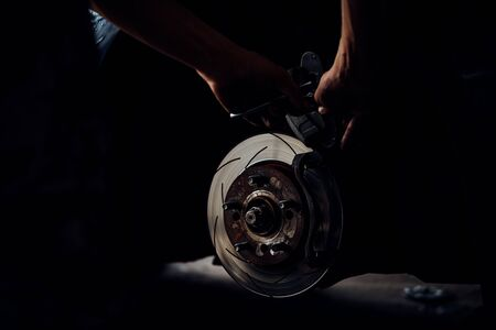 Car mechanic or serviceman checking a disc brake and asbestos brake pads it's a part of car use for stop the car for safety at front wheel