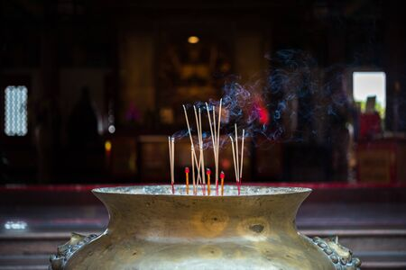 Joss stick or incense sticks burning by fire with smoke for buddhist pray for benefaction worship to Buddha at Thai or Chinese temple Stockfoto