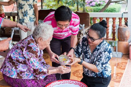 Ang Thong, Thailand - April 7, 2019 : Unidentified Asian people bathe respectation to elderly parents by water with jasmine, rose flower and aromatherapy in bowl in Songkran Festival (Thai New Year)