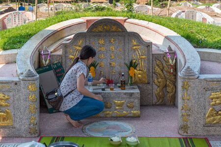 Prachinburi, Thailand - April 6, 2019 : Thai Chinese respect ancestors parents those died by food and burn fake money to sacrifice them at cemetery in Qingming Festival (Qing Ming), Tomb-Sweeping Day