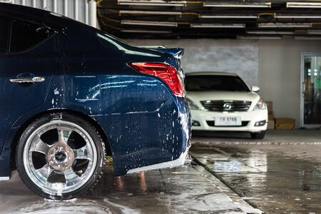 Bangkok, Thailand - March 23, 2019 : Unidentified car care staff cleaning (clean, wash, polish and wax) the car (Car detailing) at car care shop in Bangkok Thailand