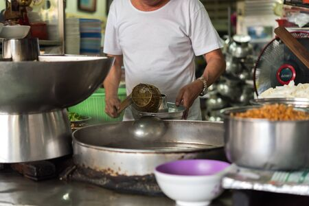 Bangkok, Thailand - March 29, 2019 : Unidentified Asian chef cooking a noodle soup with meat ball (kauy-tiew) for sale at Thai street food market or restaurant in Thailand