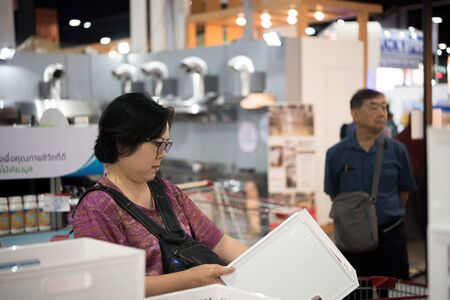 Bangkok, Thailand - March 23, 2019 : Unidentified asian woman feeling happy when her purchase a big product with cartons in shopping cart in department store or exhibit hall expo