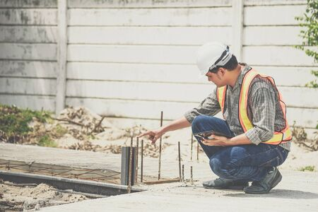 Asian man civil construction engineer worker or architect with helmet and safety vest working and holding a touchless tablet computer for see blueprints or plan at a building or construction site
