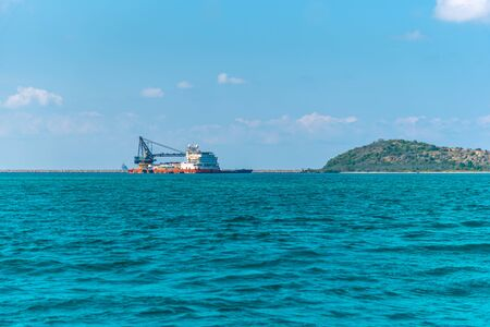 Landscape of travel place with nature at a beach and tropical sea with blue sky and have a reef and rock beach with Cargo ship or Freighter ship