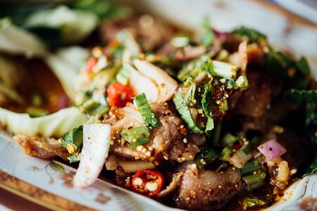 Spicy sliced grilled beef salad (Nam Tok) is a Thai food for health consists of beef, ground rice, chili, lemon, onion and herb mixed in plate on a wood table at Thai street food Imagens