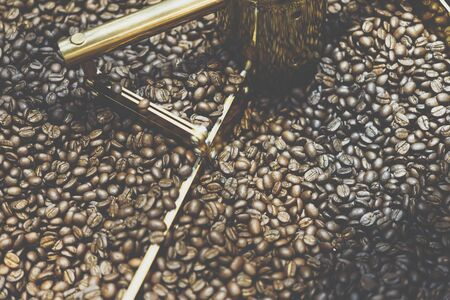 Coffee beans and roasted coffee beans roasting in roaster coffee beans machine at coffee shop cafe or restaurant
