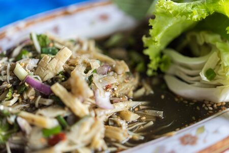 Bamboo shoot spicy salad (Soup Knor Mai) is northeastern Thai food for sale at Thai street food market or restaurant in Thailand Imagens