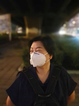 Asian woman use mask N95 respiratory protection mask against air with smog PM2.5 dust exceed the standard value of Bangkok city with bad weather air pollution on road with traffic in Bangkok