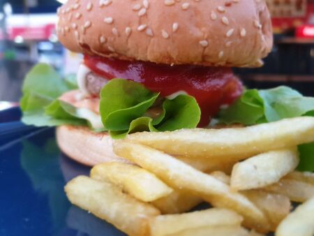 Hamburger is a fast food make from bun, meat, cheese and vegetable in fastfood restaurant, unhealthy food or fat concept