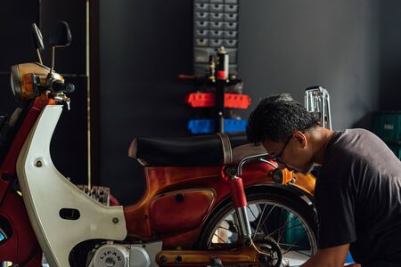 Bangkok, Thailand - March 30, 2019 : Unidentified mechanic or serviceman checking a classic retro motorcycle (Japan motorcycle vintage style) for fix and repair problem at garage or repair shop Imagens