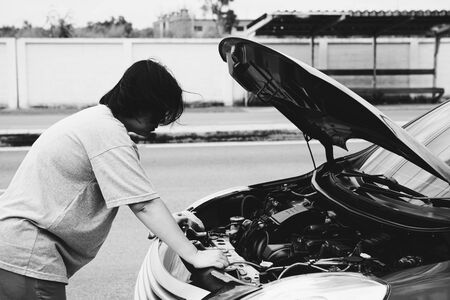 Asian woman 40s alone driver checking a car engine for fix and repair problem with unhappy and dismal between waiting a car mechanic from car engine problem at roadside Imagens