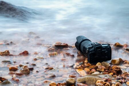 DSLR camera with telephoto lens wet from water sea wave at stone beach when travel and test using in the extreme environment demo waterproof by photographer