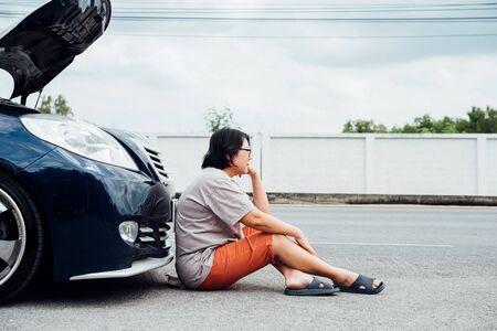 Aziatische vrouw 40s alleen bestuurder die een automotor controleert op een probleem met een oplossing en reparatie met ongelukkig en somber tussen het wachten op een automonteur van een automotorprobleem langs de weg Stockfoto