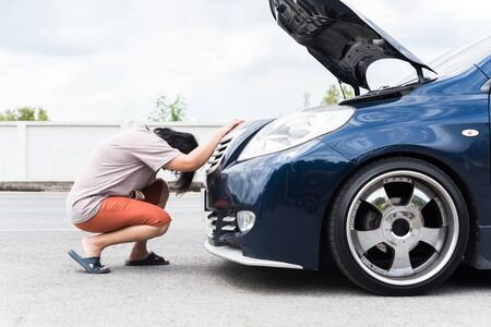 Asian woman 40s alone driver checking a car engine for fix and repair problem with unhappy and dismal between waiting a car mechanic from car engine problem at roadside