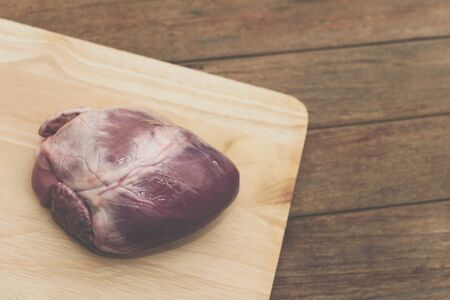 Fresh pig heart from market on wooden cutting board in kitchen for make a food have a pig heart for ingredient in restaurant