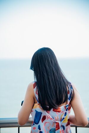 Asian pretty woman relax at sea viewpoint with loneliness and lonely emotion in concept travel, vacation, leisure in life