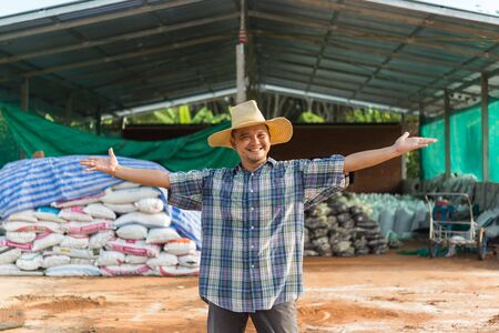 Asian man farmer agriculturist happy at a Fertilizer composting plant with Organic Fertilizer, Compost (Aerobic Microorganisms) from animal waste for use in the organic agriculture industry