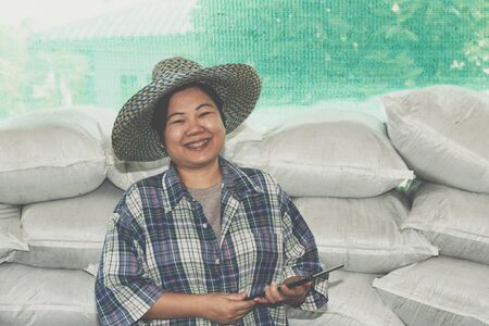 Asian woman smart farmer agriculturist happy at a Fertilizer composting plant with Organic Fertilizer, Compost (Aerobic Microorganisms) from animal waste for use in the organic agriculture industry Stock Photo