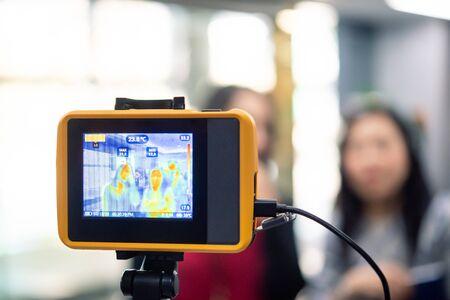 Asiatische Menschen, die auf die Überprüfung der Körpertemperatur warten, bevor sie im Büro durch Thermoscan oder Infrarot-Wärmebildkamera gegen die epidemische Grippe covid19 oder das Corona-Virus Zugang zum Gebäude haben