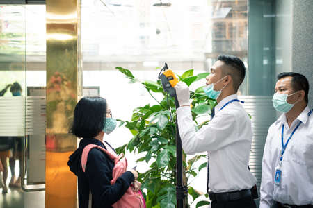 Bangkok, Thailand - March 16, 2020 : Unidentified people waiting body temperature check to access building for against epidemic flu covid19 or corona virus by thermoscan or infrared thermal camera
