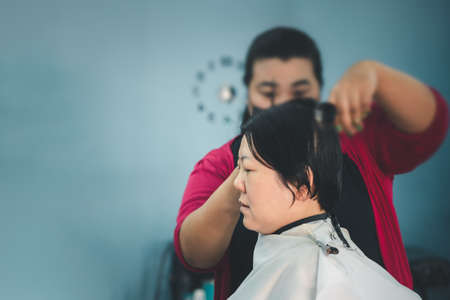 Asian woman hairdresser or hairstyle haircut a woman plump body customer in fashion hairstyle at barbershop Stock Photo