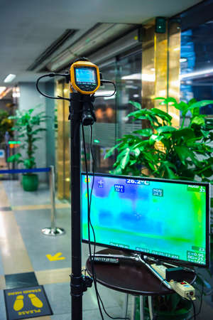 Bangkok, Thailand - March 17, 2020 : Unidentified people waiting body temperature check to access building for against epidemic flu covid19 or corona virus by thermoscan or infrared thermal camera