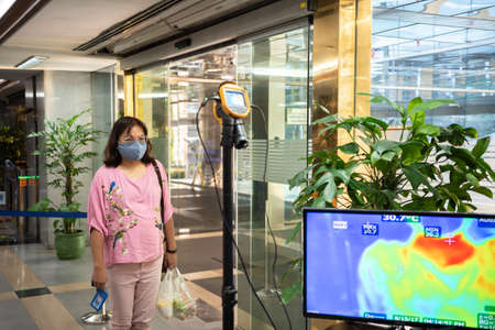 Bangkok, Thailand - March 24, 2020 : Unidentified people waiting body temperature check to access building for against epidemic flu covid19 or corona virus by thermoscan or infrared thermal camera