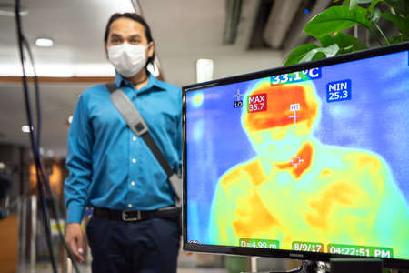 Bangkok, Thailand - March 18, 2020 : Unidentified people waiting body temperature check to access building for against epidemic flu covid19 or corona virus by thermoscan or infrared thermal camera Editorial